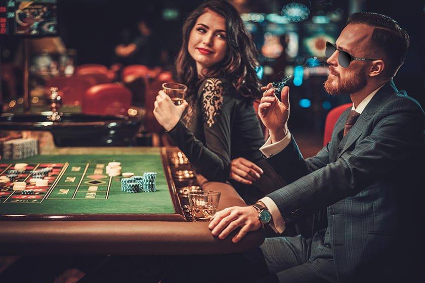 τυχερά γυαλιά ηλίου βοηθούν παίχτη στο καζίνο, μαύρα γυαλιά ηλίου black rose σε γοητευτικό άντρα στο καζίνο δίπλα σε ωραία γυναίκα